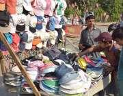 لاہور: نوجوان دھوپ کی شدت سے بچنے کے لیے ریڑھی سے ٹوپیاں خرید رہا ہے۔