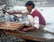 گلگت: ایک شخص دریاے انڈر کے کنارے روایتی انداز سے کار آمد اشیاء تلاش ..