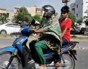 راولپنڈی: خاتون موٹر سائیکل سوار مری روڈ سے گزر رہی ہے۔