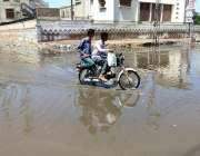 حیدر آباد: موٹر سائیکل سوار بارش کے جمع شدہ پانی سے گزر رہے ہیں۔