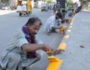 لاہور: کربلا گامہ شاہ کے سامنے مزدور ڈیوائیڈر پر رنگ و روغن کر رہے ہیں۔