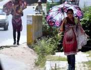 راولپنڈی: خواتین دھوپ کی شدت سے بچنے کے لیے چھتری تانے جا رہی ہیں۔