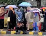 راولپنڈی: بارش کے دوران ٹرانسپورٹ کی کمی کے باعث طالبات چھتری تانے ..