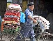 راولپنڈی: محنت کش پھیری لگا کر چادریں وغیرہ فروخت کر رہا ہے۔