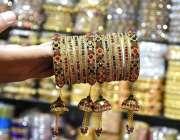 لاڑکانہ: دکاندار گاہکوں کو متوجہ کرنے کے لیے چوڑیاں سجا رہاہے۔
