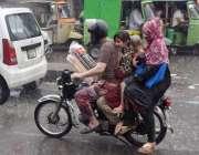 لاہور: ایک موٹر سائیکل سوار فیملی موسلا دھار بارش میں اپنی منز ل کی ..