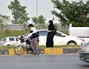 اسلام آباد: موٹر سائیکل سوار غلط طریقے سے سٹرک کراس کر رہا ہے جو کسی ..