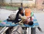 لاہور : ایک خانہ بدوش خاتون اپنے کمسن بچے کے ہمراہ آرام کی غرض سے گدھار ..