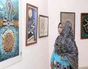 لاہور: ایک خاتون الحمرا ہال میں خطاطی کی نمائش دیکھ رہی ہے۔