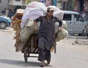 راولپنڈی:ایک محنت کش ہاتھ ریڑھی پر سامان رکھ کر کھینچتا ہوا جا رہاہے۔
