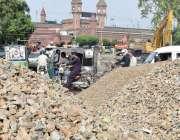 لاہور: ریلوے اسٹیشن کے سامنے سڑک کی مرمت کے لیے پتھر پڑے ہیں۔