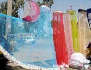 راولپنڈی: سڑک کنارے ایک محنت کش نے مچھردانیاں فروخت کے لیے سجا رکھی ..