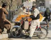 لاہور: ایک شہری ریڑھی والے سے مالٹے خرید رہا ہے۔