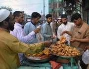پشاور: شہری افطاری کے لیے ایک دکان سے پکوڑے خرید رہے ہیں۔