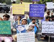 لاہور: شہری کینسر کی ادویات کی بندش کے خلاف مطالبات کی تحریر والے کتبے ..