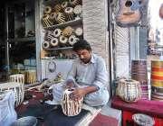 راولپنڈی: ایک دکاندار سڑک کے کنارے میوزک کے آلے ڈھولکی تیار کررہا ہے۔