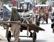 لاہور: ایک محنت کش ہتھ ریڑھی پر سامان رکھے جا رہا ہے۔