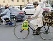 لاہور: ایک شحص گھر کا چولہا جلانے کے لیے لکڑیاں اکٹھی کر کے سائیکل پر ..