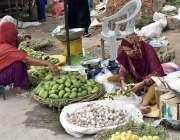 فیصل آباد: محنت کش خاتون گاہکوں کو متوجہ کرنے کے لیے اچاری آم کاٹ رہی ..