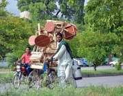 اسلام آباد: محنت کش سائیکل پر سٹول اور ٹیبل وغیرہ رکھے فروخت کے لیے ..