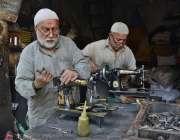 لاہور: محنت کش اپنی ورکشاپ میں سلائی مشینیں مرمت کر رہے ہیں۔