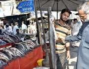 فیصل آباد: جھنگ بازار میں اپنی دکان پر صارفین کو راغب کرنے کے لئے مچھلیاں ..
