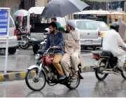 را ولپنڈی: موٹر سائیکل سوار بارش سے بچنے کے لیے چھتری تانے جار ہاہے۔