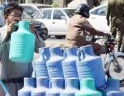 لاہور: ایک محنت کش فلٹر پانی فروخت کے لیے بوتلوں میں بھر کر لیجا رہا ..