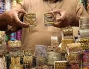 لاہور: دکاندار گاہکوں کو متوجہ کرنے کے لیے چوڑیاں سجا رہاہے۔