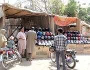 لاہور: کینال روڈ پر لگے سٹال سے شہری ہیلمٹ خرید رہا ہے۔