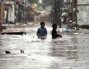 راولپنڈی: شہر میں ہونے والی موسلا دھار بارش کے بعد جمع شدہ پانی سے بچے ..