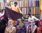 لاڑکانہ: عید کی تیاریوں میں مصروف خواتین ایک دکان سے کپڑا خرید رہی ہیں۔