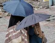 اسلام آباد: خواتین نے بارش سے بچنے کے لیے چھتری تان رکھی ہے۔