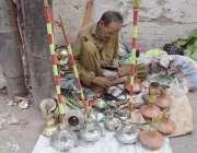 لاہور: اندرون شہر میں ایک محنت کش حقے مرمت کررہاہے۔