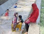 لاہور: بچیاں گرمی کی شدت کم کرنے کے لیے نہر سے ملحقہ کھالے میں نہا رہی ..