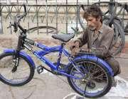 لاہور: نیلا گنبد مارکیٹ میں ای کاریگر سائیکل مرمت کر رہا ہے۔