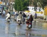 ملتان: موٹر سائیکل سوار شجاع آباد روڈ پربارش کے جمع شدہ پانی سے گزر ..