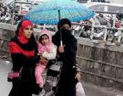 ر اولپنڈی: خواتین نے بارش سے بچنے کے لیے چھتری تان رکھی ہے۔