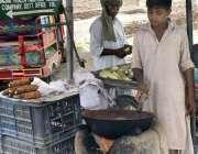 فیصل آباد: محنت کش بچہ گھر کی کفالت کے لیے چھلیاں روسٹ کر رہا ہے۔