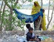حیدر آباد: خانہ بدوش خاتون اپنے بچوں کو دھوپ کی شدت سے بچانے کے لیے کپڑے ..