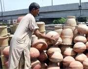لاہور: دکاندار گاہکوں کو متوجہ کرنے کے لیے مٹی کے برتن سجا رہاہے۔