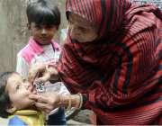 لاہور: پولیو مہم کے دوان لیڈی ہیلتھ ورکر ایک بچے کو پولیو کے قطرے پلا ..