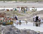 نوشہرہ: سیر و تفریح کے لیے آئے شہری جھیل کے قریب بیٹھے ہیں۔