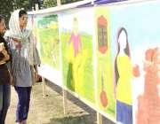 لاہور: لڑکیاں جیلانی پارک میں طالبات کی تیار کردہ پینٹنگس دیکھ رہی ..
