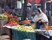 سیالکوٹ: خاتون سڑک کنارے لگے سٹال سے فروٹ خرید رہی ہے۔