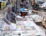 لاہور: ایک محنت کش نے کتابوں اور اخباروں کا سٹال سجا رکھا ہے۔
