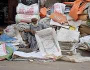 لاہور: ایک بزرگ محنت کش لوگوں سے خریدے گئے پلاسٹک کے توڑے ترتیب سے رکھ ..