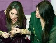 لاہور: ایک خاتون عیدالفطر کی تیاری کے لیے اپنی ساتھ کے ہاتھ پر مہندی ..