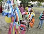 لاہور: ایک محنت کش سائیکل پر غبارے فروخت کررہا ہے۔