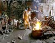 حیدرآباد: ایک لوہار اپنے کام کی جگہ پر لوہا پگھلانے میں مصروف ہے۔